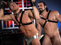 Athletic Alexander Gustavo's wrist restraints are tied to a spreader cane hanging above his head. Beefcake Jaxton Wheeler, covered in a full rubber uniform, spanks Alexander's ass, leaving his ass cheeks with a pink tinge. Grabbing an anal massager, Jaxto daddy gay porn